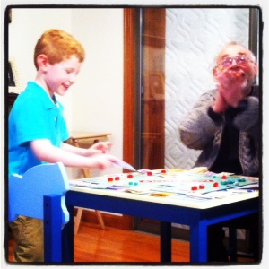 5-year old Jeremy playing Monopoly with his grandpa.